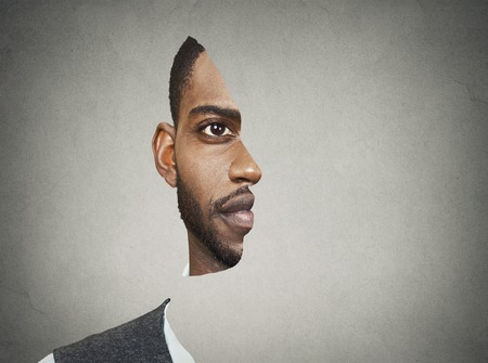 Optical illusion surrealistic portrait front with cut out profile of a young man isolated on grey wall background