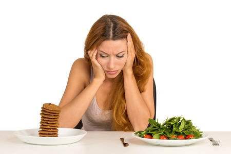 tired: Young woman tired of diet restrictions deciding whether to eat healthy food or sweet cookies she is craving sitting at table isolated white background. Human face expression emotion. Nutrition concept