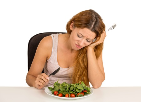 bad diet: Young woman tired of diet restrictions deciding whether to eat healthy food craving sweet cookies sitting at table isolated white  background. Human face expression emotion. Nutrition concept Stock Photo