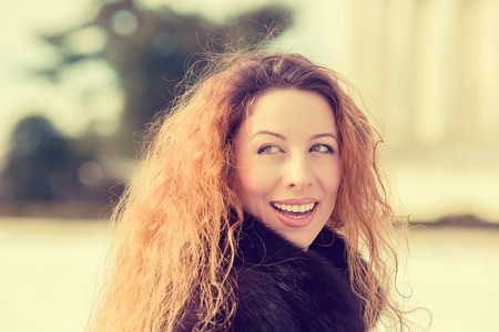Outdoors portrait of young cheerful beautiful woman having fun in winter spring. Positive face expression photo