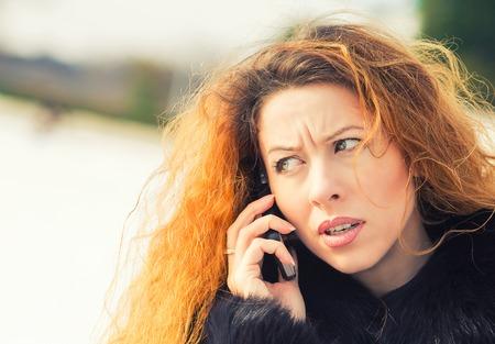 expresiones faciales: Retrato del primer trastorno triste, esc�ptico, infeliz, mujer seria hablando por tel�fono, al aire libre de pie. Las emociones negativas humanos, las expresiones faciales, los sentimientos, la vida de reacci�n. Percepci�n Malas noticias