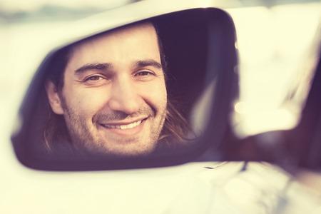 hombre manejando: Conductor joven feliz que mira en la cara del coche retrovisor, asegurándose de que la línea esté libre antes de hacer un giro. Positivas emociones expresión cara humana. Viaje Viaje seguro concepto de conducción