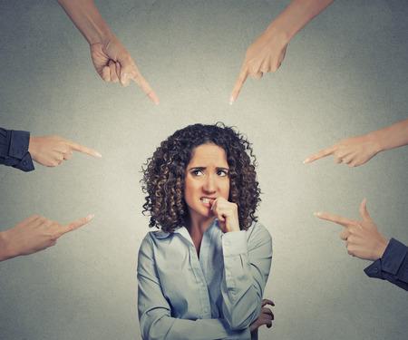 conflictos sociales: Concepto de denuncia social de la empresaria culpable muchos dedos apuntando al aislados sobre fondo gris de la pared de la oficina. Retrato asustado mujer avergonzada ansioso morderse las u�as