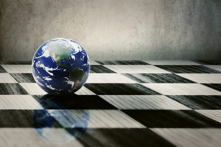 foreign policy: world earth on a chessboard isolated on grey wall background. Elements of this image furnished by NASA
