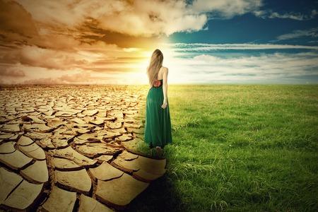 気候変動のコンセプト イメージ。緑の草と極端な乾燥した干ばつ土地の風景