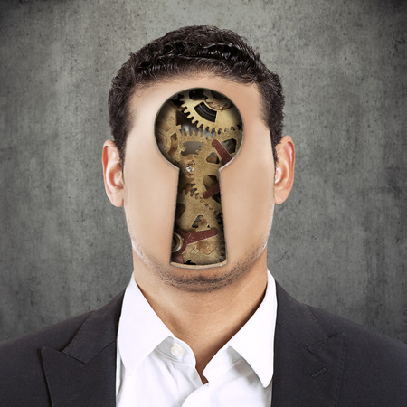 Closeup headshot young faceless man with keyhole and gear mechanism instead of face isolated on grey black texture office wall background photo