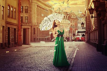 古い町の路上で屋外で立ってお金雨の下で傘を持つ若い女性を興奮させた。肯定的な感情の経済的な成功運良い経済の概念 写真素材
