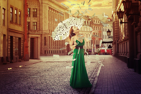 Excited young woman with umbrella under a money rain standing outdoors in old town on a street. Positive emotions financial success luck good economy concept