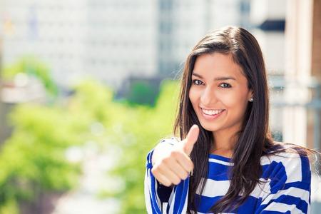 jovenes estudiantes: Hermosa mujer feliz con los pulgares para arriba aislados en el fondo de la ciudad. Cara positiva percepci�n vida expresi�n Foto de archivo