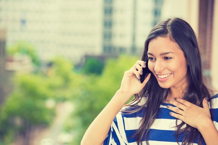 indian beauty: Young happy excited laughing woman talking on mobile phone isolated outdoors city urban background.