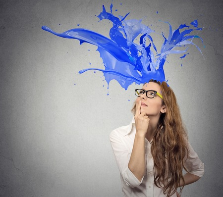 Thoughtful businesswoman looking up with colorful splashes coming out of her head isolated on gray wall background. Face expression perception