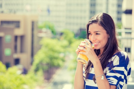urban life: Closeup portrait beautiful happy woman enjoying sunny day off on a balcony of her apartment drinking orange juice on a urban city background. Positive face expressions emotions healthy lifestyle