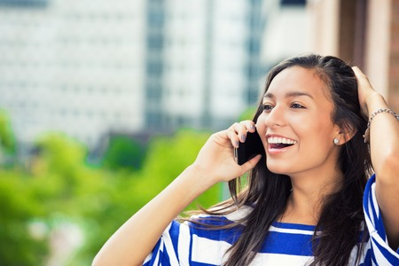 colombian: Young happy excited laughing woman talking on mobile phone isolated outdoors city urban background.