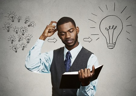 brainy: Intelligence knowledge. Closeup portrait smart handsome man student holding a book scratching head has big ideas isolated on gray wall background. Face expression attitude life perception dynamism Stock Photo
