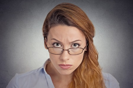 skepticism: Skepticism. Angry grumpy doubtful woman looking at you camera isolated on grey wall background. Negative human emotion facial expression feeling body language attitude Stock Photo