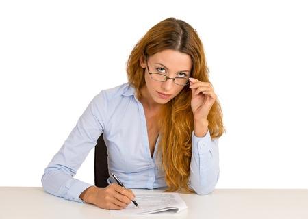 expresion corporal: Empresaria seria con gafas con escepticismo mirarte sentado en el escritorio de la oficina aislada en el fondo blanco. Expresión del rostro humano, el lenguaje corporal, la actitud