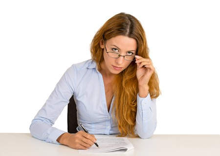 evaluating: Serious businesswoman with glasses skeptically looking at you sitting at office desk isolated on white background. Human face expression, body language, attitude