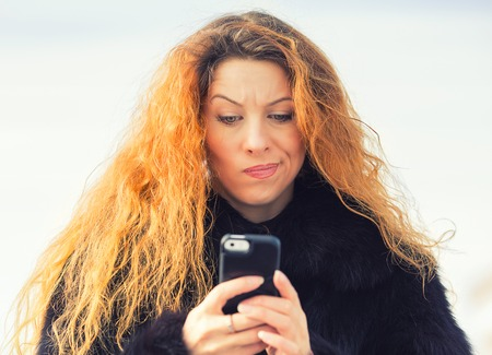Closeup portrait upset sad skeptical unhappy serious woman talking texting on mobile phone displeased with conversation isolated outdoor background. Negative human emotion face expression feeling Stock Photo