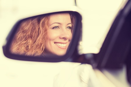 mirror face: Happy young woman driver reflection in car side view mirror. Positive human face expressions, emotions. Safe winter trip, journey driving concept Stock Photo