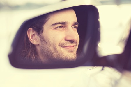 from side: Portrait happy young man driver reflection in car side view mirror. Guy driving his new car. Positive human face expression emotions. Safe trip journey driving concept Stock Photo