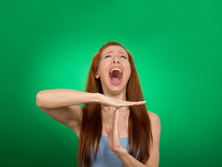 arbitros: Mujer joven que muestra el tiempo de espera gesto de la mano, frustrado que grita a stop aisladas sobre fondo verde. Demasiadas cosas que hacer. Las emociones humanas se enfrentan reacción expresión