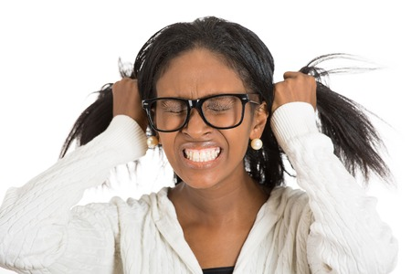 dolor de cabeza: Frustrado subrayó mujer con gafas. Headshot niña abrumada infeliz tiene dolor de cabeza mal día saca su pelo fondo blanco aislado. La emoción negativa sentimientos expresión cara percepción Foto de archivo