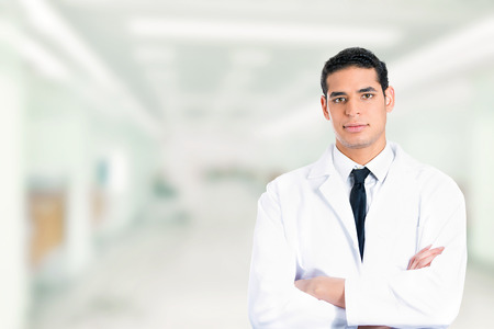 Portrait of friendly confident male doctor smiling arms folded standing in hospital clinic hallway corridor photo