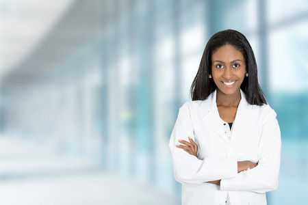 pharmacist: Portrait confident African American female doctor medical professional standing isolated on hospital clinic  hallway windows background. Positive face expression Stock Photo