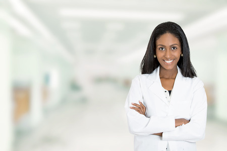 Portrait confident African American female doctor medical professional standing isolated on hospital clinic  hallway windows background. Positive face expression Stock Photo