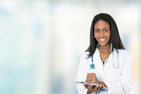doctor clipboard: Portrait confident African American female doctor medical professional writing patient notes isolated on hospital clinic hallway windows background. Positive face expression