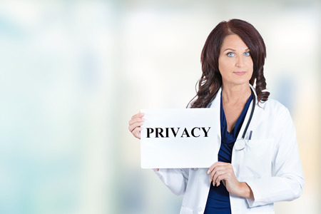 confidentiality: Female healthcare professional doctor scientist researcher pharmacist holding privacy sign isolated hospital windows background. Confidentiality patient care medical record information HIPAA concept Stock Photo