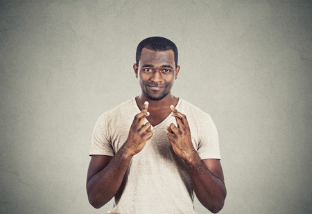 crossing fingers: Young hopeful man crossing fingers isolated on grey wall background. Human face expression