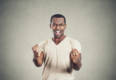 expression: Closeup portrait happy successful young student man winning, fists pumped celebrating success isolated grey wall background. Positive human emotion, facial expression. Life perception, achievement