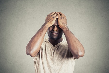 conflicto: Retrato del primer chico molesto infeliz, joven triste molestado por errores manos en los ojos de la cabeza cerrados aislados sobre fondo gris de la pared. Cara emoci�n negativa expresi�n