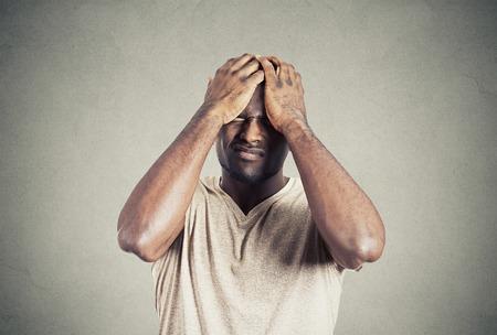 occhi tristi: Ritratto del primo piano infelice ragazzo sconvolto, triste giovane disturbato da errori mani sulla testa occhi chiusi isolato su sfondo grigio muro. Emozione negativa espressione faccia