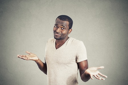 Young man shrugging shoulders who cares so what I dont know gesture isolated on grey wall background. Body language