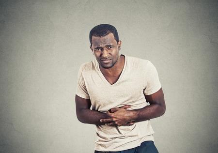 dolor de estomago: Hombre no saludable, doblándose de dolor de estómago mirando mal enfermo infeliz enfermo, aislado sobre fondo gris de la pared