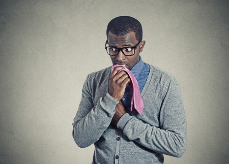 nervous: Portrait geeky nervous anxious businessman bitting chewing his tie