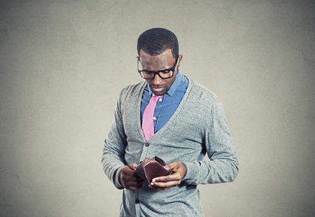 Hombre joven que mira en su cartera vacía no tiene dinero