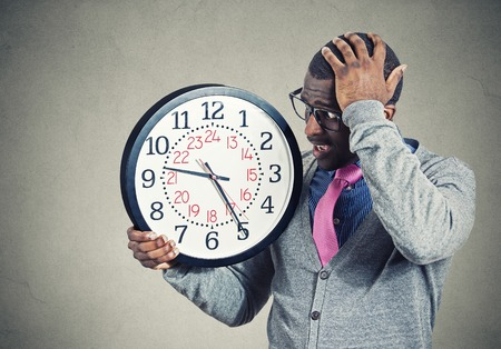 end of a long day: Stressed young man running out of time looking at wall clock