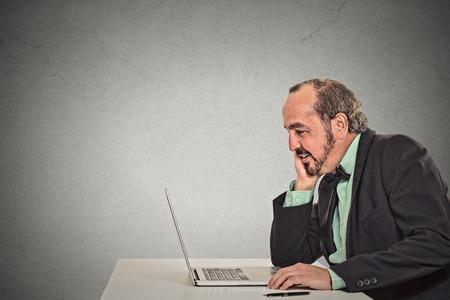 Man working reading something on his laptop computer photo