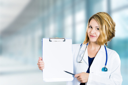 care providers: Happy smiling doctor holding clipboard standing in hospital hallway isolated on clinic windows background