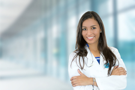 female face: Portrait confident young female doctor medical professional standing isolated on hospital clinic hallway windows background. Positive face expression