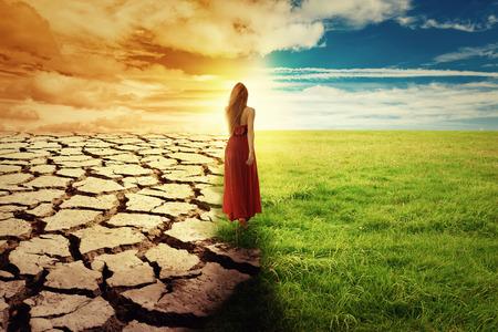 気候変化のコンセプト イメージ。緑の草や干ばつ土地の風景です。オープン フィールドを歩く緑のドレスを着た女性