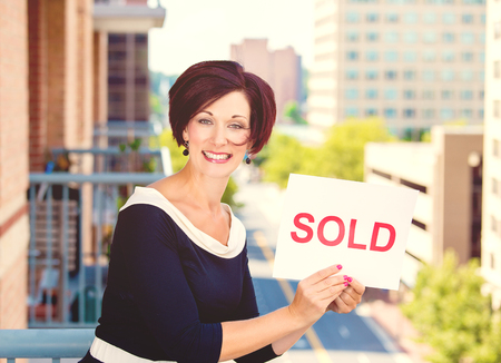 sold sign: Real estate agent holding sold sign isolated on city background. Positive face expression