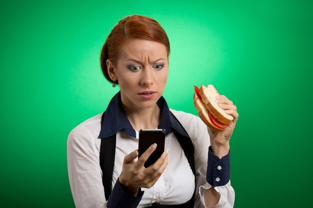 myth: Portrait young worried business woman looking at her mobile phone eating bread sandwich on the go isolated on green background