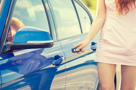 Young woman presses unlock button on car remote control unlocks door alarm systems. Vehicle convenience safety security system Stockfoto