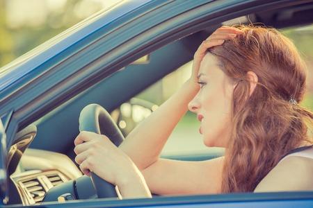 Vue de côté fenêtre portrait déplut jeune souligné colère énervé femme conduite automobile gêné par le trafic lourd. Concept de l'intelligence émotionnelle. Expression négative de visage humain