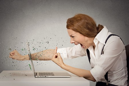 hatred: Side profile angry furious businesswoman throws a punch into computer, screaming. Negative human emotions, facial expressions, feelings, aggression, anger management issues concept Stock Photo