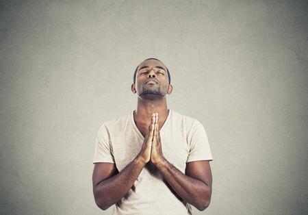 Close-up portret jonge man bidden handen hoop voor de beste om vergeving te vragen of wonder geïsoleerde grijze muur achtergrond. Menselijke emotie gezichtsuitdrukking gevoel Stockfoto